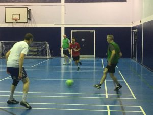 4 men playing football indoors